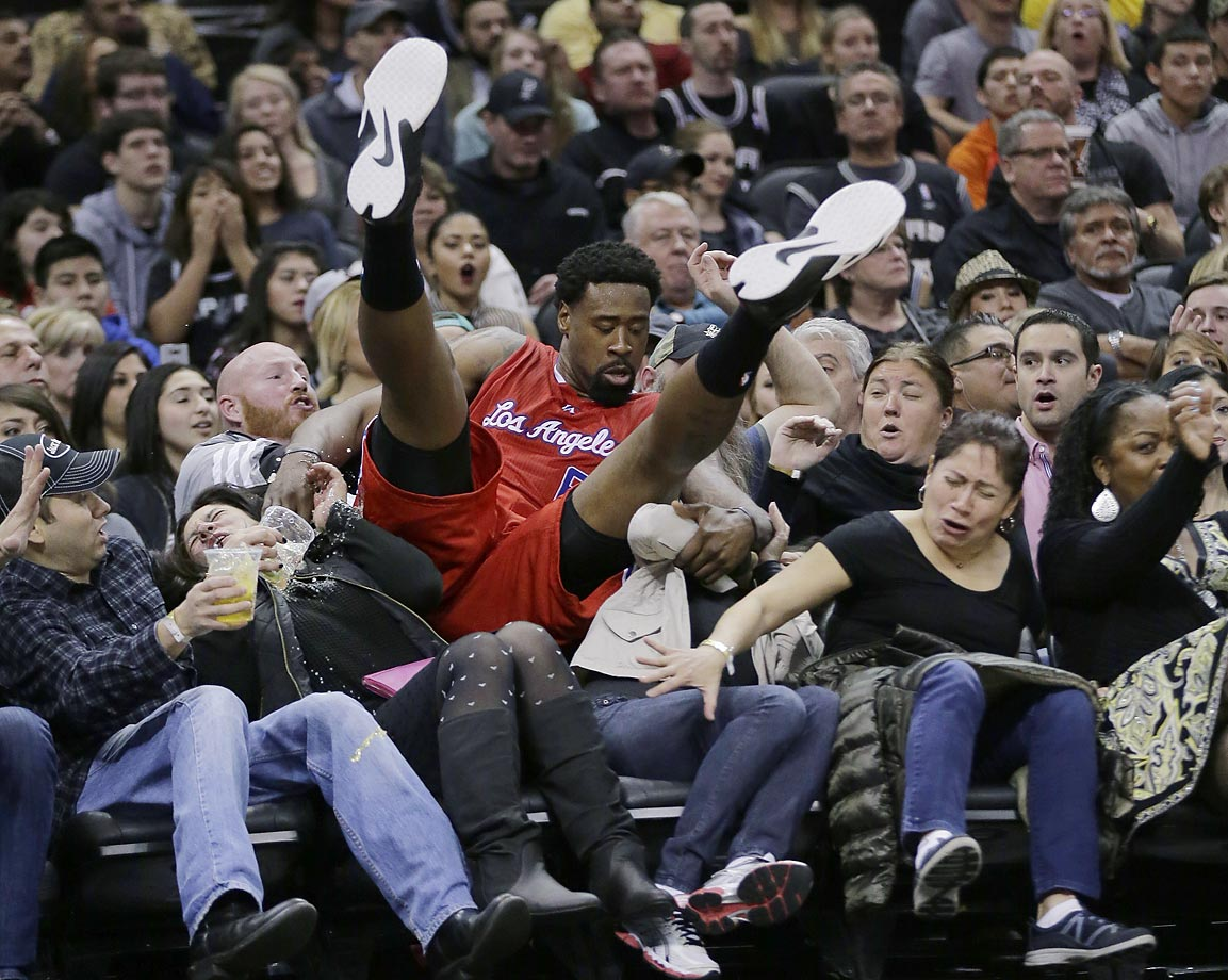 DeAndre Jordan of the Clippers falls into the row of fans during a game against the Spurs.