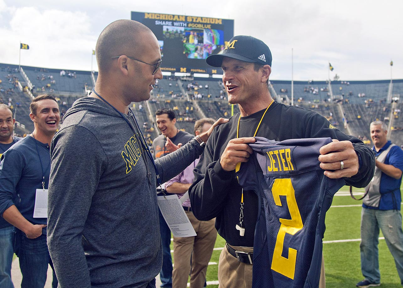 Derek Jeter receives a gift from Jim Harbaugh at Michgan's game against BYU. Jeter graduated high school in Kalamazoo, Mich., and was offered a scholarship to play baseball for Michigan.