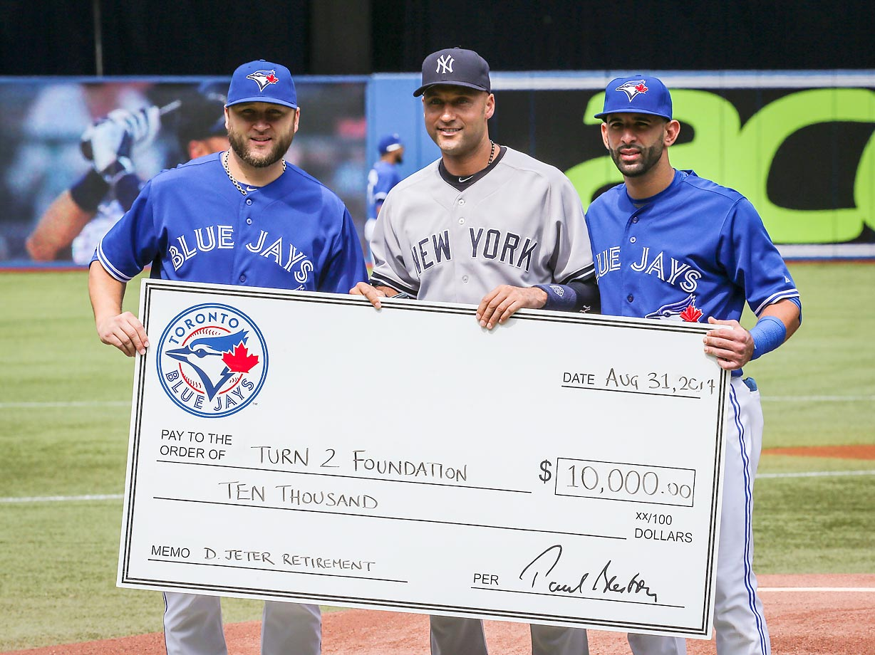 Derek Jeter accepts a check for $10,000 for his Turn 2 Foundation from Toronto Blue Jays players Mark Buehrle and Jose Bautista.