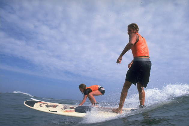 Joshua Paskowitz teaches a camper how to stand on a surf board.