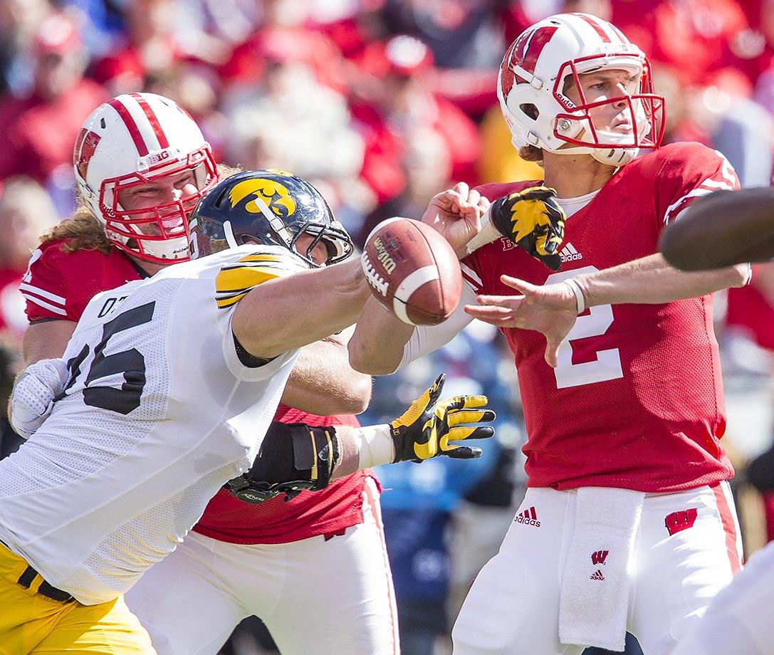 Drew Ott of Iowa knocks the ball loose from Wisconsin quarterback Joel Stave.