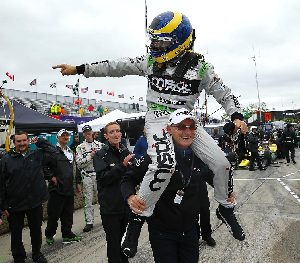 Sebastien Bourdais celebrates on the shoulders of his father, Patrick, after winning the second race of the IndyCar Detroit Grand Prix.