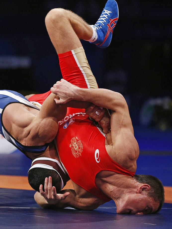 Artem Surkov of Russia (red) is taken down by Migran Arutyunyan of Armenia during their Greco-Roman 66 kg bronze medal wrestling match at the wrestling world championships in Las Vegas.