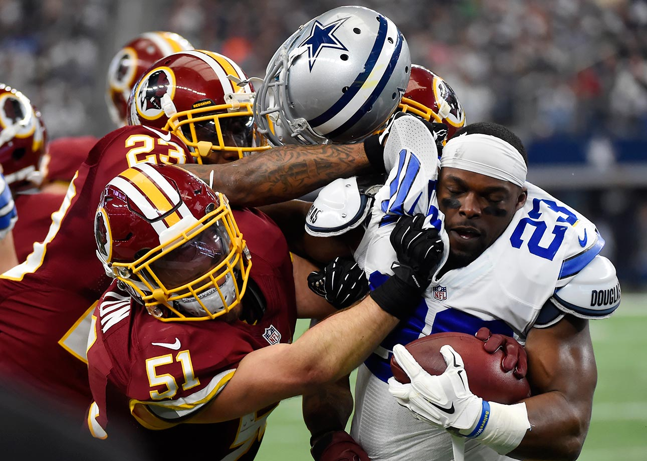 Will Compton and DeAngelo Hall of Washington knock the helmet off Robert Turbin of the Dallas Cowboys.