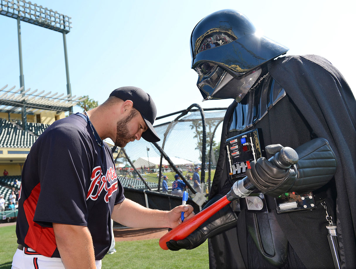 Atlanta Braves catcher Evan Gattis autographs a lightsaber bat for Darth Vader before a spring training game on March 15, 2013 at Champion Stadium at ESPN Wide World of Sports Complex in Lake Buena Vista, Fla.