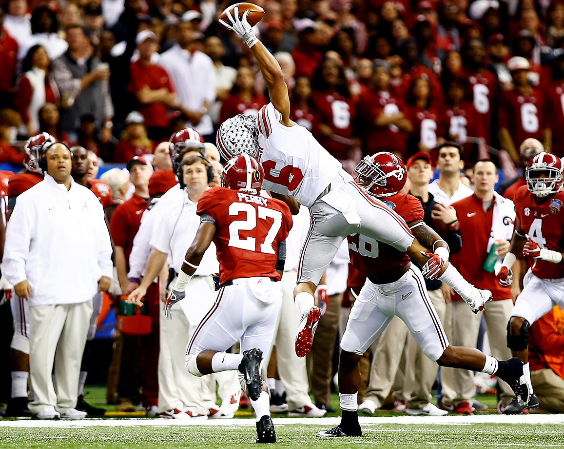Wide receiver Evan Spencer of the Ohio State Buckeyes reaches over defensive back Nick Perry of the Alabama Crimson Tide during their playoff semifinal at the Mercedes-Benz Superdome in New Orleans.
