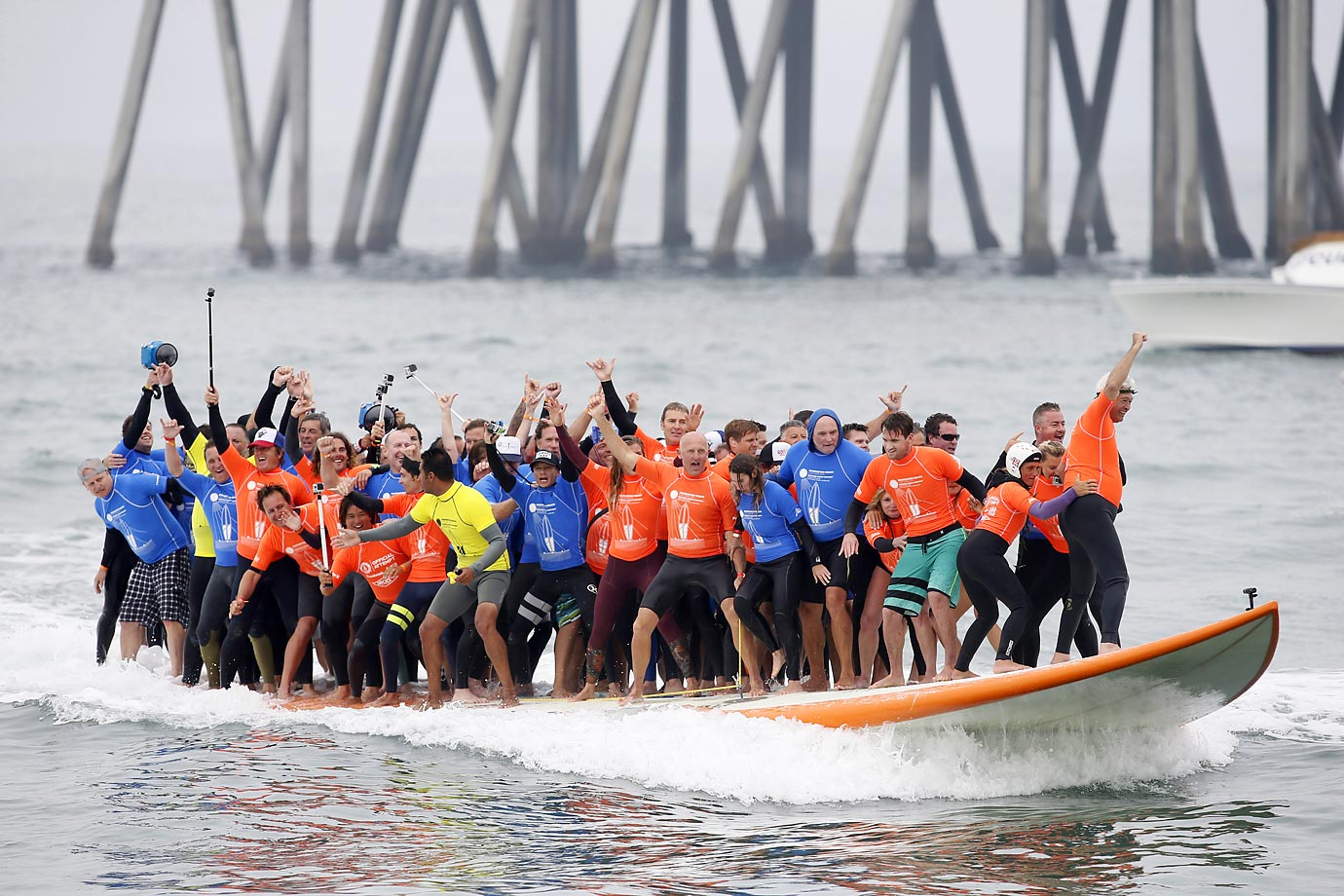 Sixty-six surfers from around the world ride a custom-built, 42-foot, 1,300-pound surfboard for 12 seconds to break the Guinness World Record in Huntington Beach, Calif.
