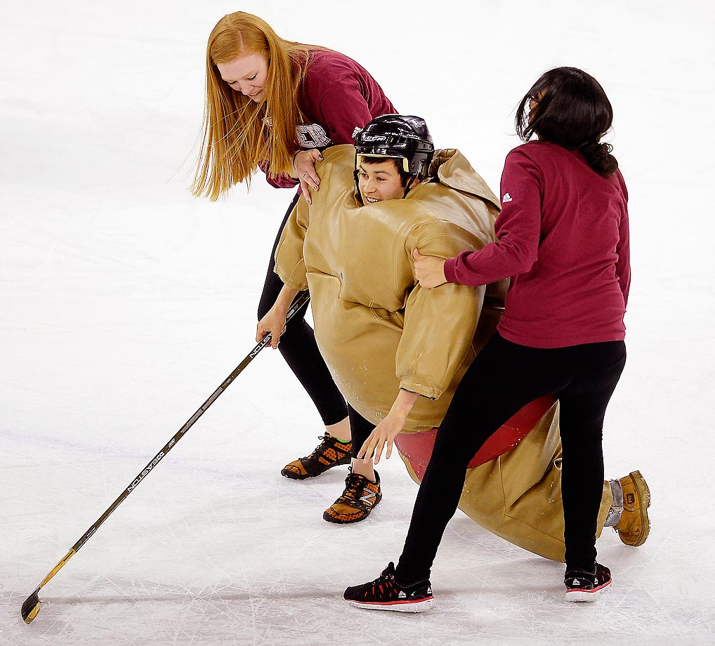 A boy in a sumo costume is helped to his feet during a special intermission event at the game between the University of Denver and St. Cloud State.