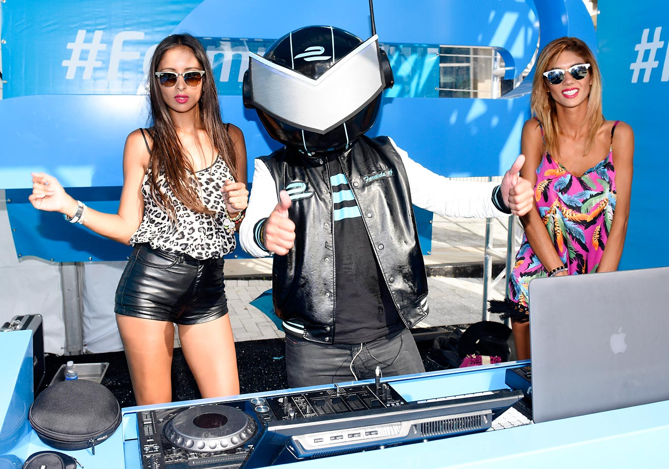A Formula DJ called EJ performs with two women during the FIA Formula E Miami ePrix race in the streets of downtown Miami.