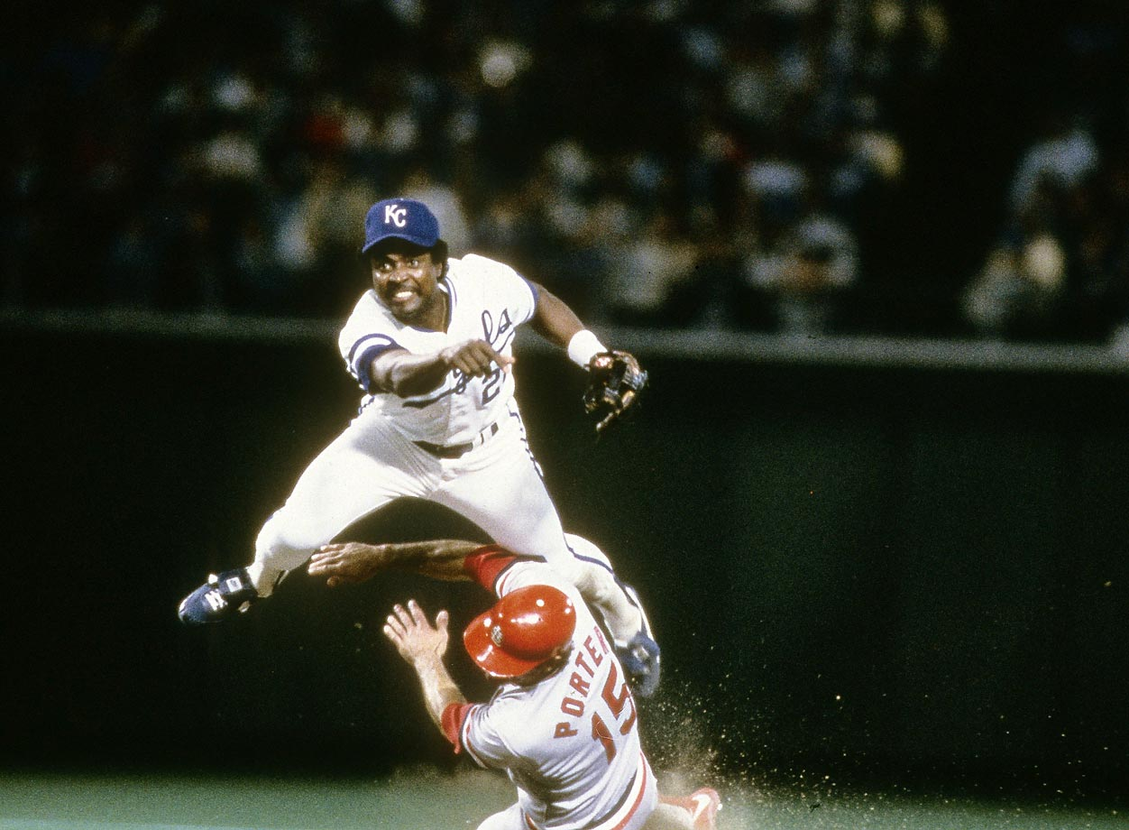 Frank White throws to first as Darrell Porter of the Cardinals slides into second.