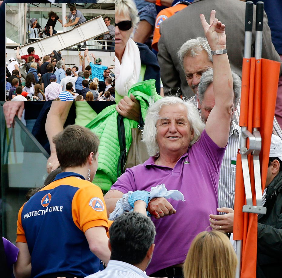 An injured spectator waves to the crowd after a metal panel fell on center court at the French Open.  Organizers say that three people were slightly injured by the falling piece of metal that detached in strong winds.