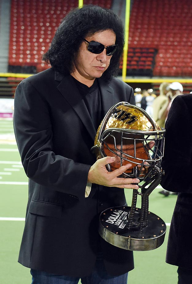 Gene Simmons, owner of the Los Angeles Kiss, holds a rivalry trophy on the field before his team's game against the Las Vegas Outlaws.