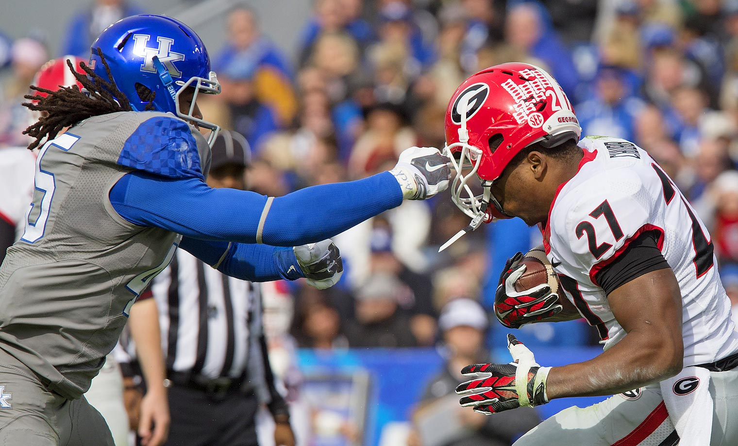 Kentucky linebacker Josh Forrest grabs the helmet of Georgia running back Nick Chubb. The Georgia Bulldogs beat the Kentucky Wildcats 63-31.