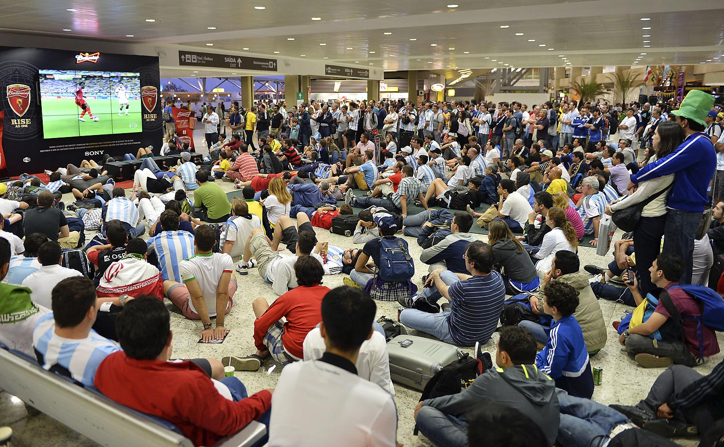 Travelers watch the match between Germany and Ghana on a screen in the departure lobby at the airport in Belo Horizonte, Brazil.
