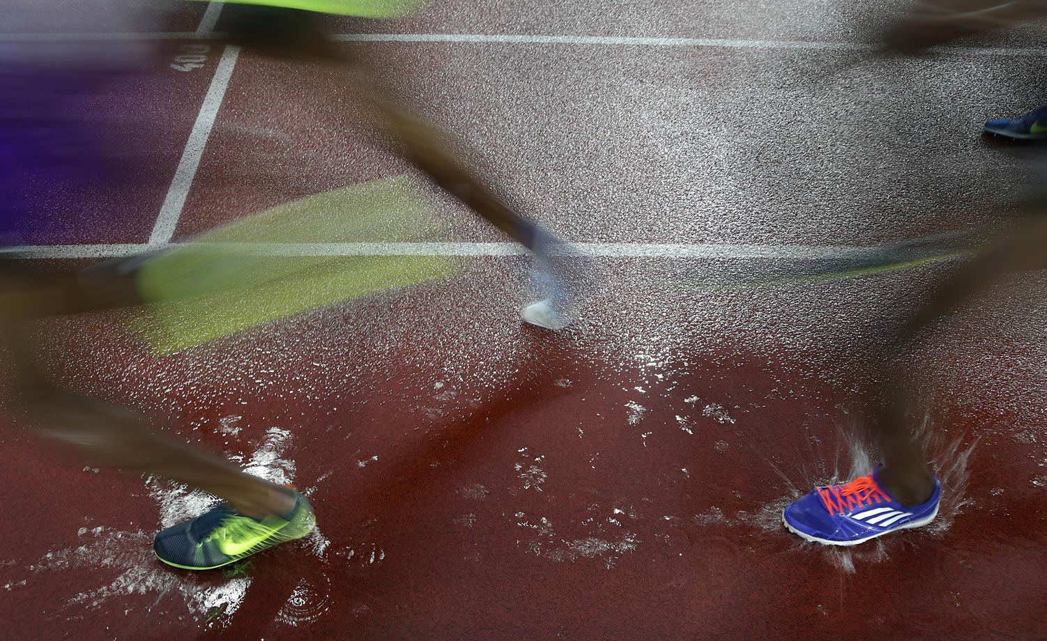 Athletes run through a puddle during the 5,000-meters event at the Golden Spike Athletic Meet.