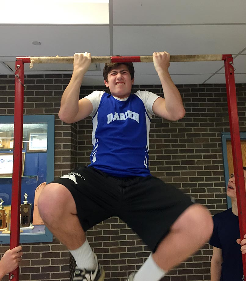 Darien High athlete Ryan Sullivan gives it his all at the pull-up bar challenge featured at the event. The ceremony was held on the same day as an eight-team track meet at Staples.