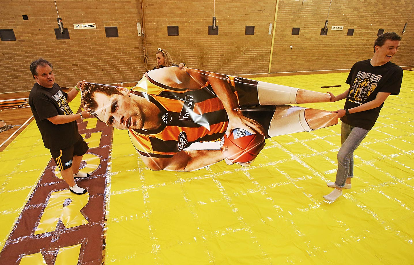 Members of the Hawthorn Hawks AFL cheersquad carry a large photo of captain Luke Hodge before the 2015 AFL Grand Final.