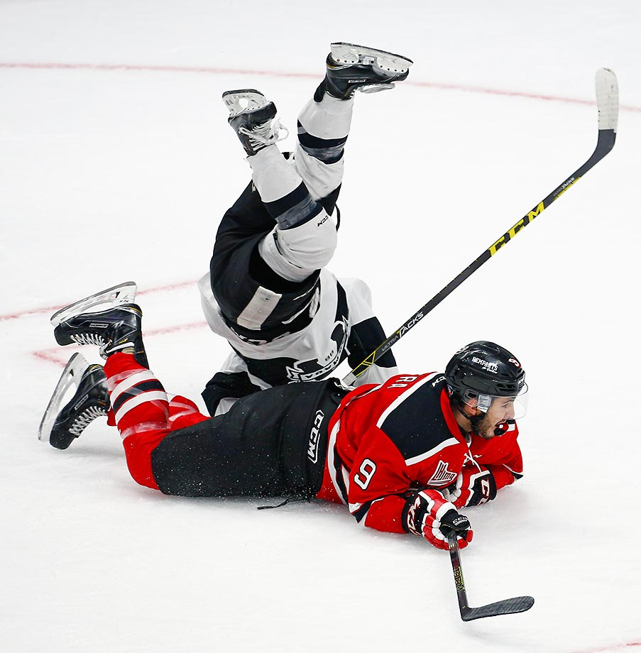 Philippe Sanche of Blainville-Boisbriand Armada trips over Aaron Dutra of Quebec Remparts during a CHL hockey game.
