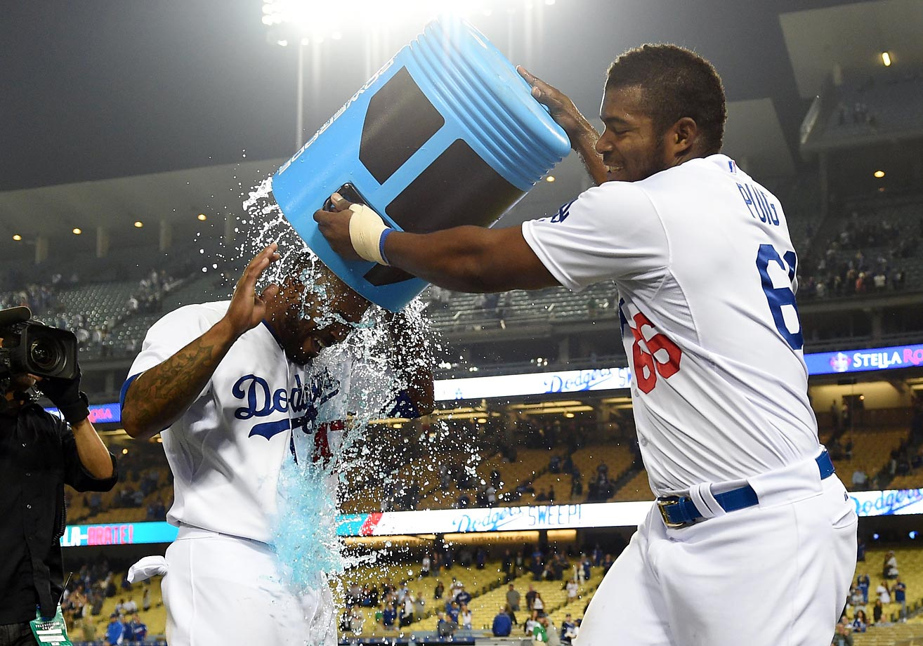 Yasiel Puig congratulates teammate Howie Kendrick with a Powerade shower after his game-winning base hit on June 10.
