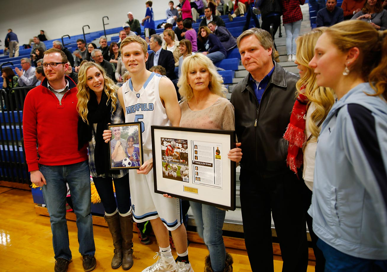 Jack poses with his family, including parents Debbie and Jack Cadigan, with a photo of Lourdina and a framed copy of the issue of Sports Illustrated he appeared in earlier this month.