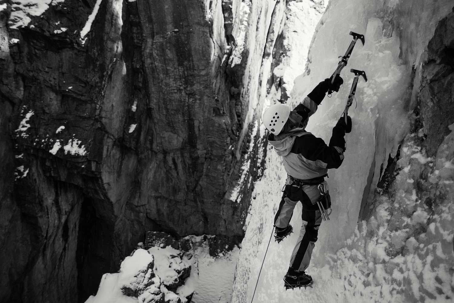 An ice climber scales a very vertical ice wall with picks and rope.