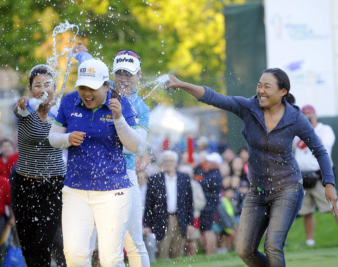 Jenny Shin (left), Meena Lee (center) and Illhee Lee spray champion Inbee Park after she won the Wegmans LPGA golf championship on Sunday. Park won in a sudden death playoff round.