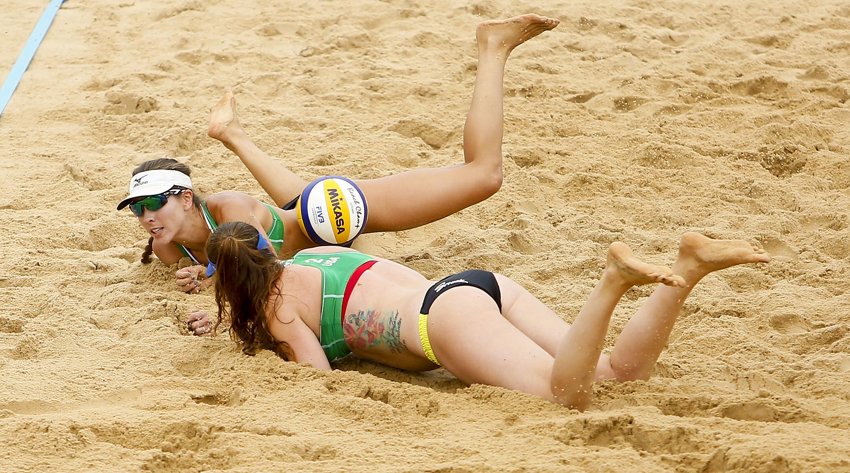 Irene Hester and Caitlin Ledoux of the U.S. dive for the ball during a match against Brazil.