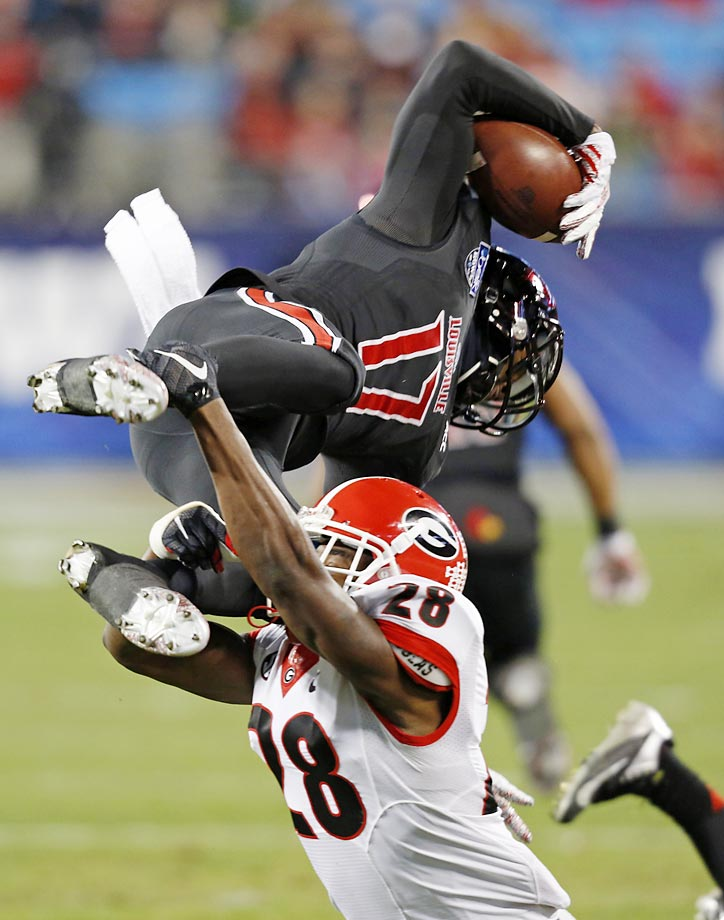 Louisville's James Quick is upended by Georgia's Kyle Vagher during the Belk Bowl  in Charlotte.