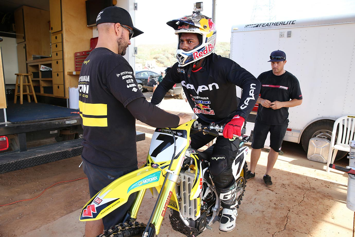 James Stewart mounts his bike with his crew making the last-minute adjustments for a practice run.