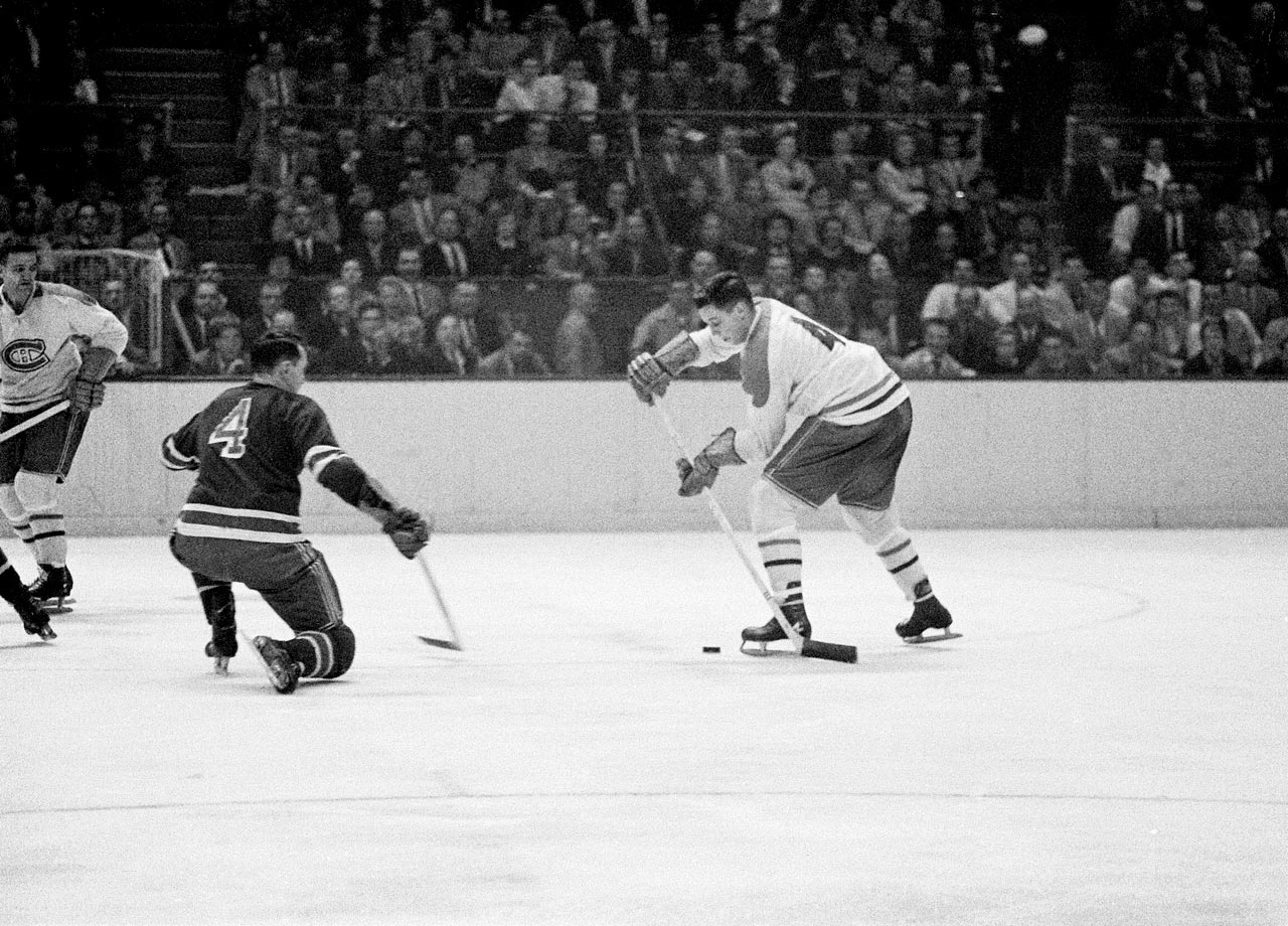Jean Béliveau looks to shoot the puck past Rangers defenseman Bill Gadsby during a game in New York on Oct. 24, 1956.