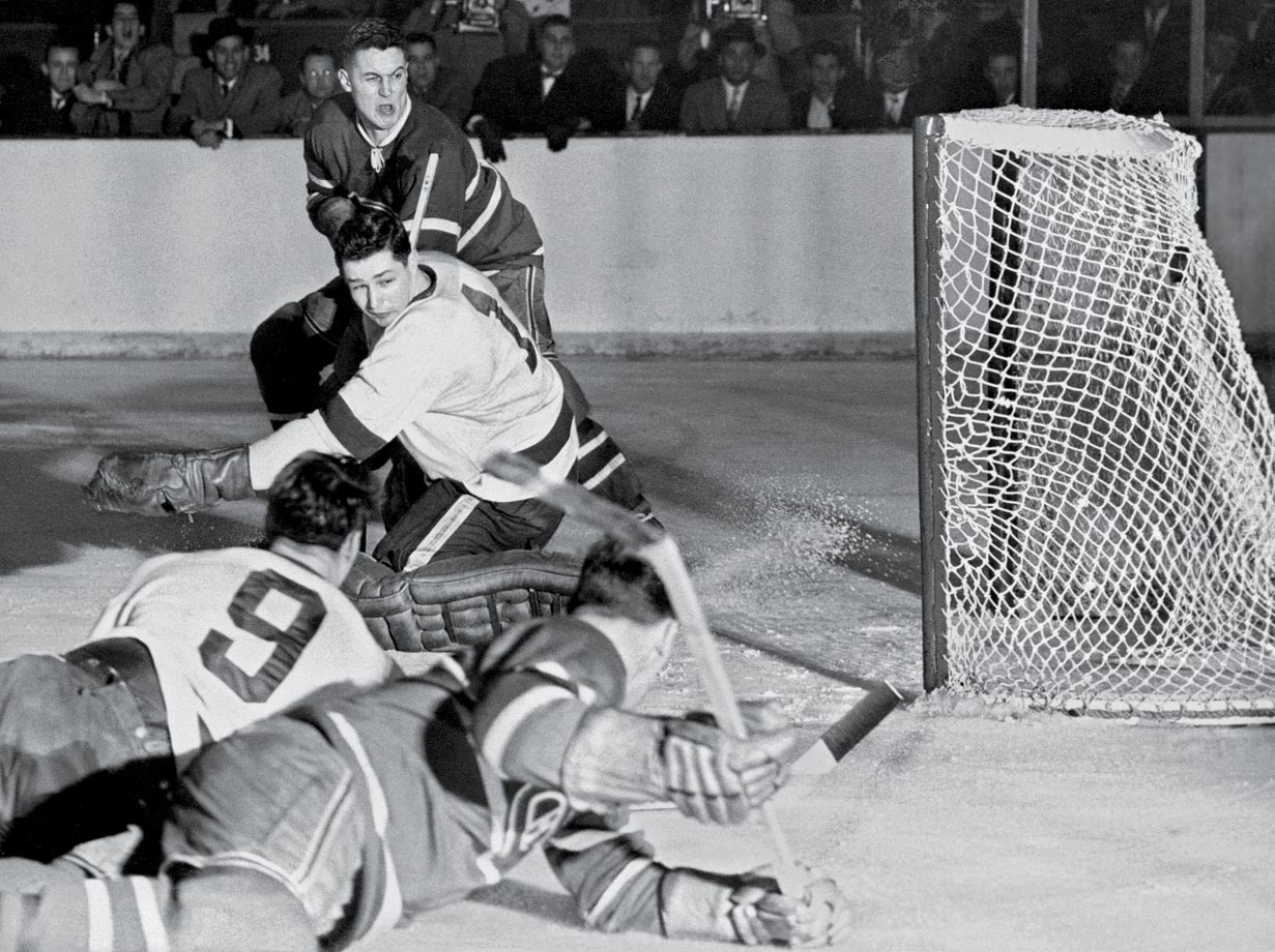 Jean Béliveau shoots the puck past Red Wings goalie Glenn Hall as Gordie Howe (9) and Henri Richard sprawl on the ice in the second period of Game 5 of the Stanley Cup Final on April 10, 1956. Montreal won the game 3-1, taking the Cup.