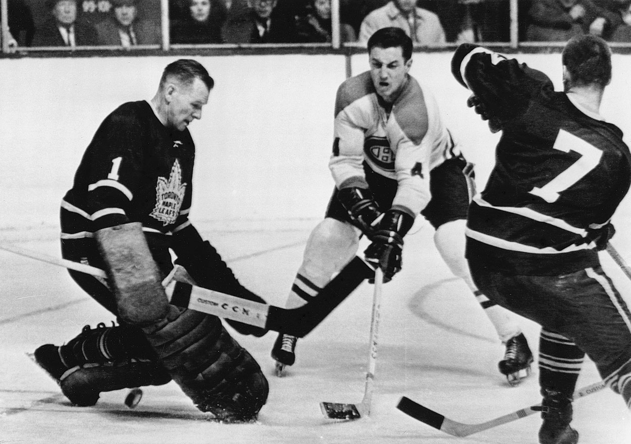 Jean Béliveau flicks the puck between the legs of Maple Leafs goalie Johnny Bower as defenseman Tim Horton looks on during a game on Feb. 22, 1967 in Toronto.