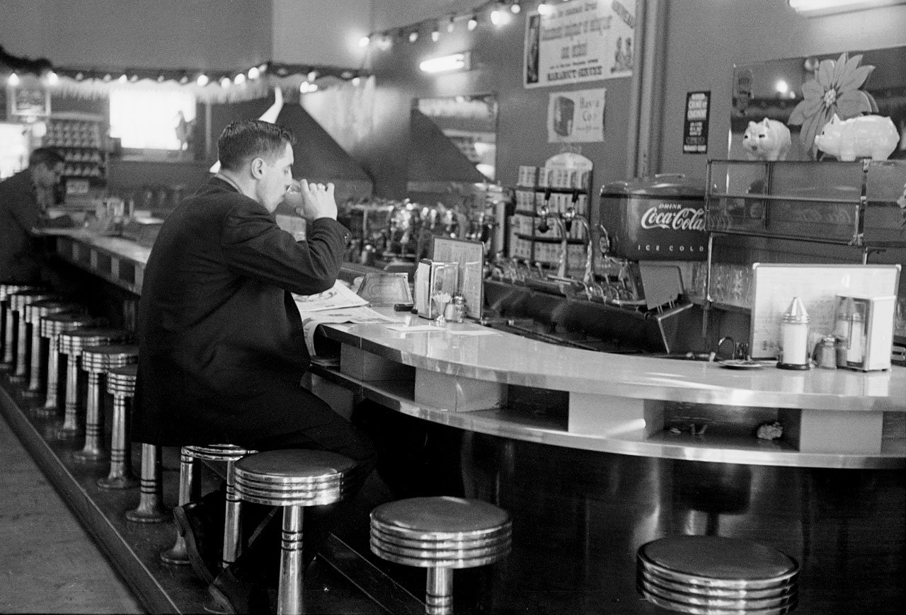 Jean Béliveau reads a newspaper at the counter of a diner in Montreal in Dec. 1952.