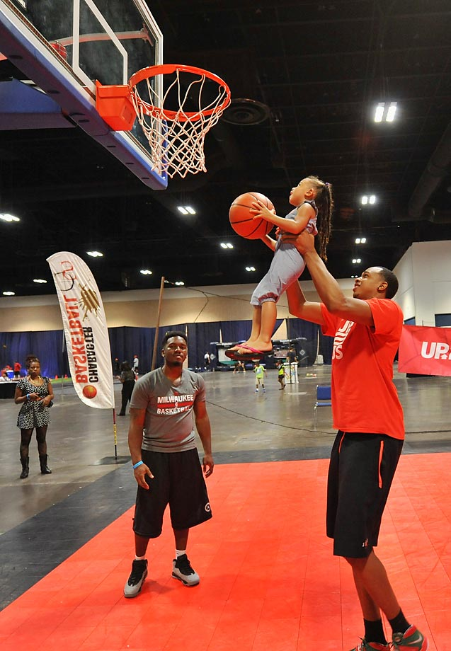 Milwaukee Bucks forward John Henson lifts a young girl for a dunk at the John Henson Experience clinic benefitting Up2Us at the Tampa Bay Youth Sports Expo.