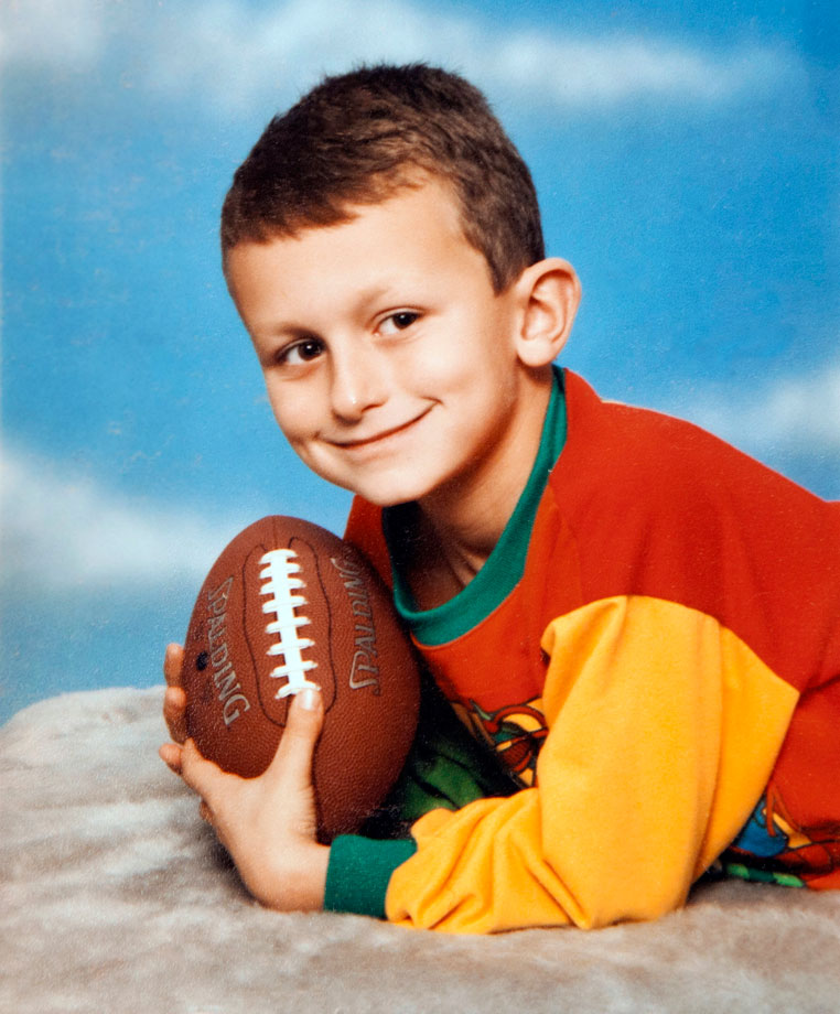 Johnny Manziel at 4 years old, holding a football in his hands.