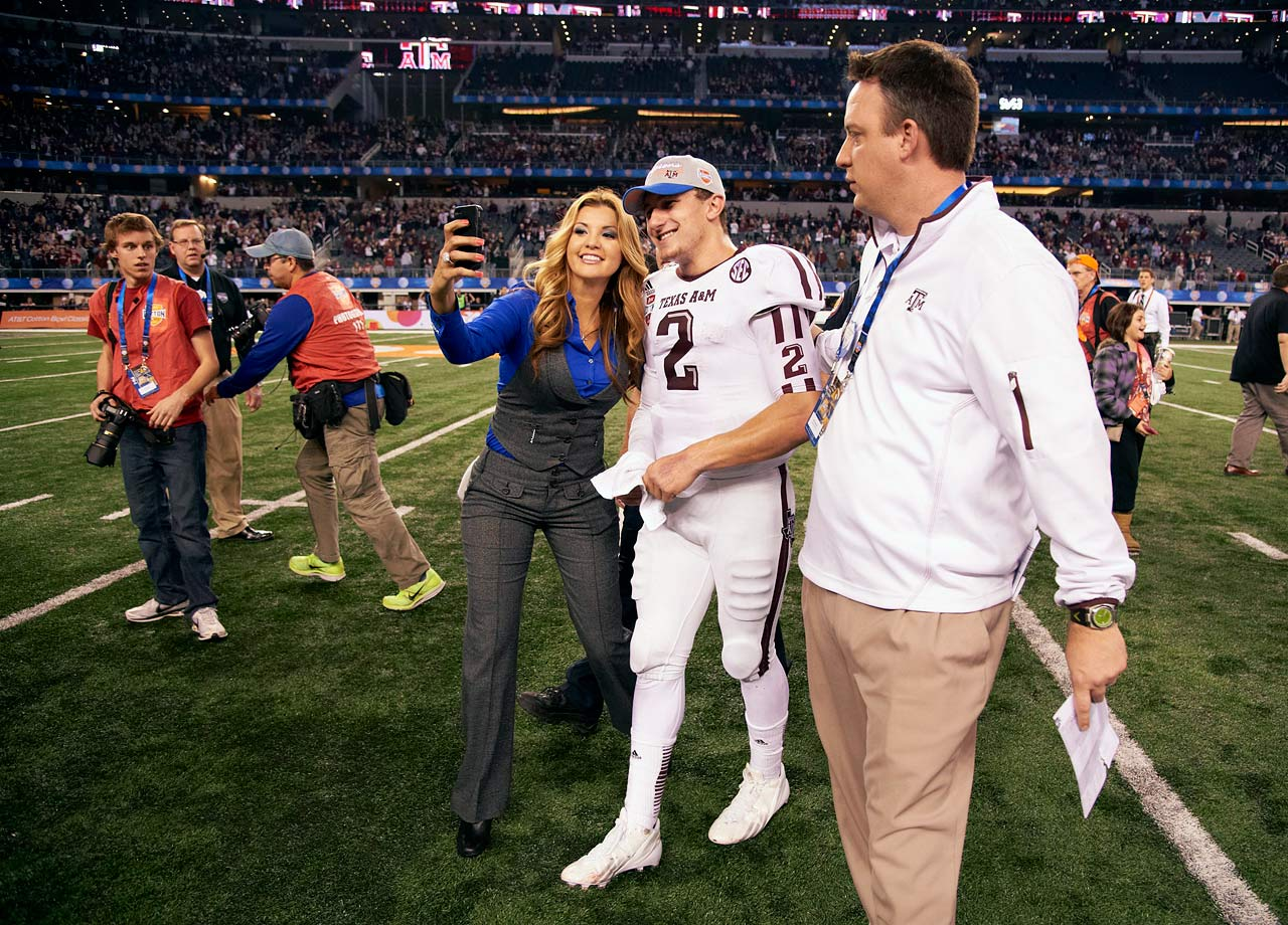 Johnny Manziel stops to pose for a photo with a credentialed fan after Texas A&M beat Oklahoma 41-13 in the Cotton Bowl.