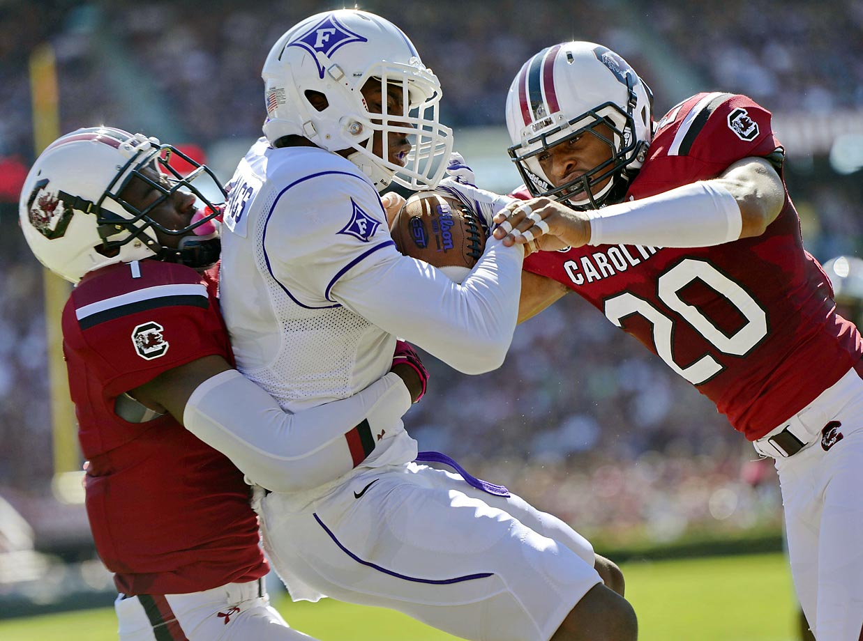 South Carolina's Rico McWilliams and T.J. Gurley try to bring down Furman wide receiver Jordan Snellings. South Carolina won 41-10.