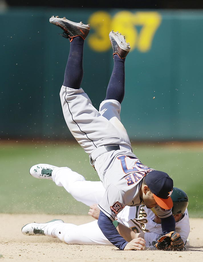 Jose Altuve of the Houston Astros is upended by Max Muncy of the Oakland A's.