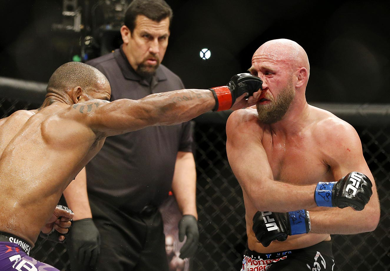 Hector Lombard hits Josh Burkman during their welterweight mixed martial arts bout at UFC 182 in Las Vegas.