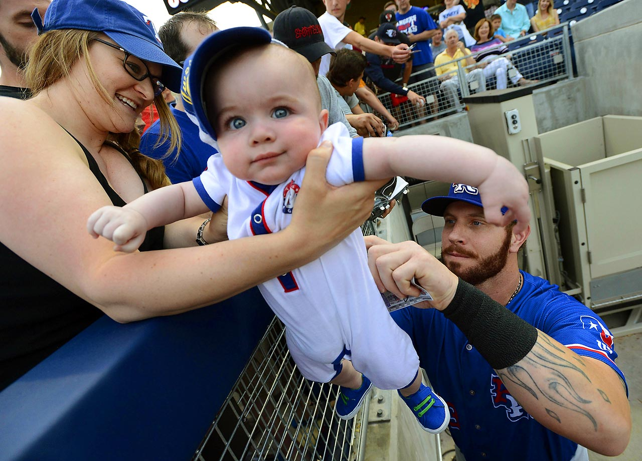 Josh Hamilton of the Rangers signs an autograph on the of back of 6-month-old Drew Hooker.  Hamilton is playing for the Round Rock Express AAA minor league team during rehab.