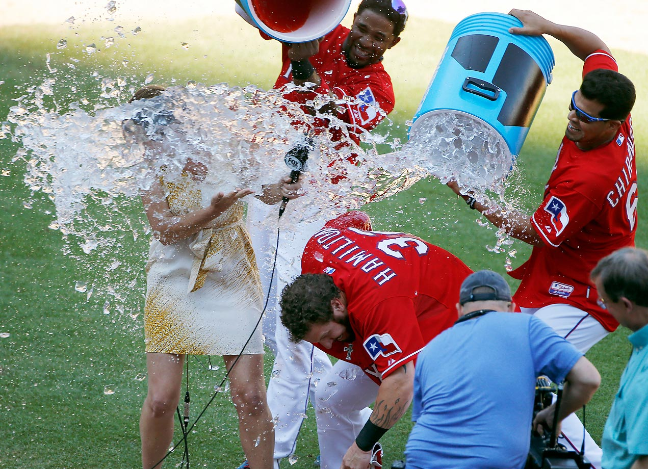 Elvis Andrus, and Robinson Chirinos of the Texas Rangers douse  Josh Hamilton and TV announcer Emily Jones after a win against the Boston Red Sox.