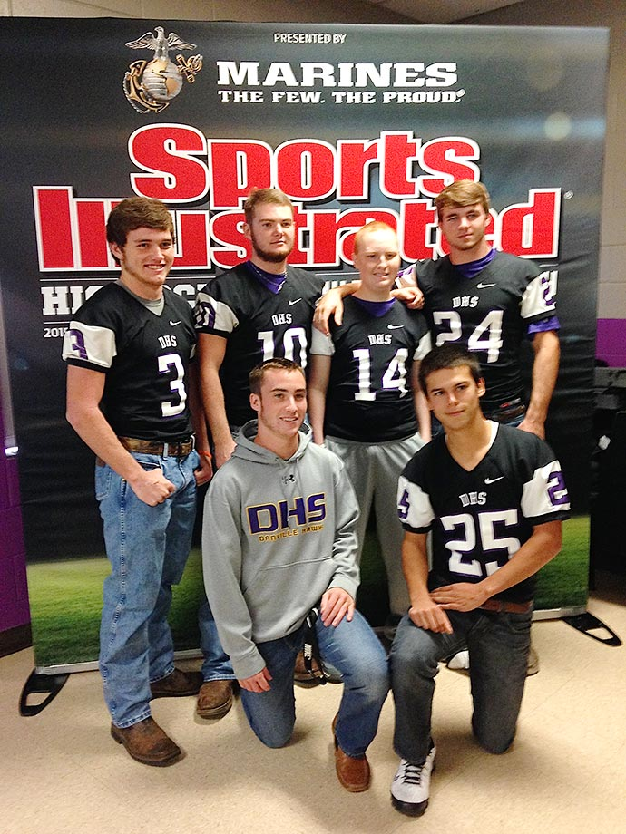 "Danville (Ala.) High fullback Kane Hogan (#14) was diagnosed with leukemia in January but has continued to show up at games and practices to cheer on and motivate his football team. Here he smiles with some teammates for a souvenir photo on the ""cover"" of SI."