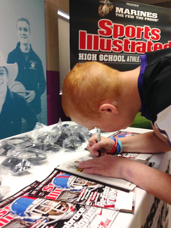 Kane Hogan signs a copy of the issue of Sports Illustrated in which he appeared.