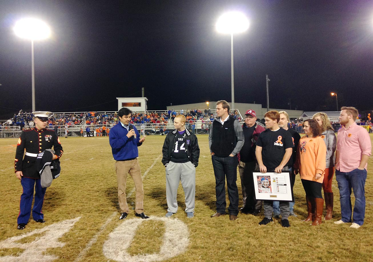 SI managing editor Chris Stone addresses Kane and his family (far right), at midfield during halftime as Sgt Lucas Spann of the U.S. Marine Corps and former Alabama quarterback John Parker Wilson look on.