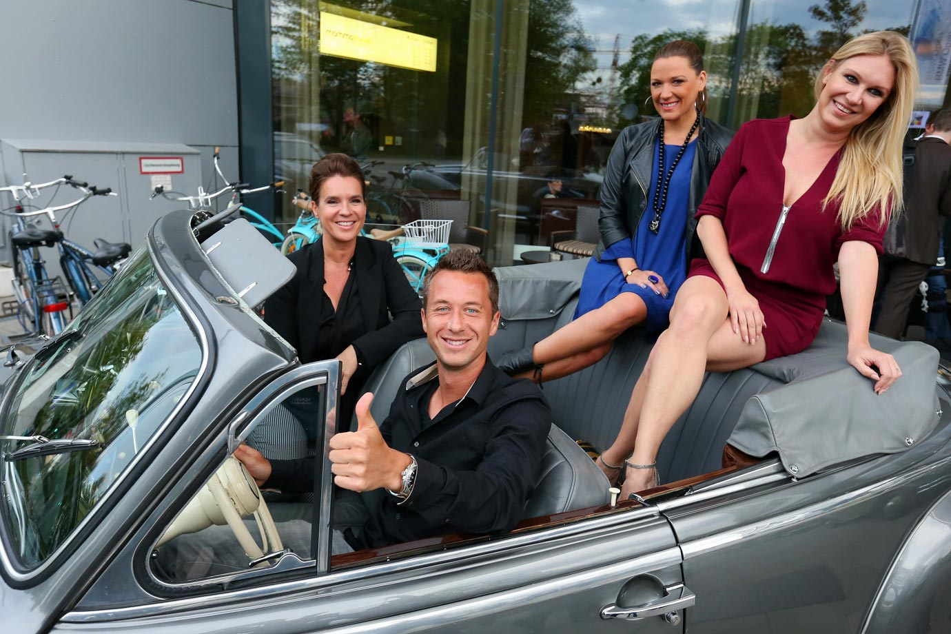 Katarina Witt, tennis star Philipp Kohlschreiber, Simone Ballack and Magdalena Brzeska sit in a historical BMW at the Iphitos Tennis Club 100 years celebration prior to the BMW Open in Munich.