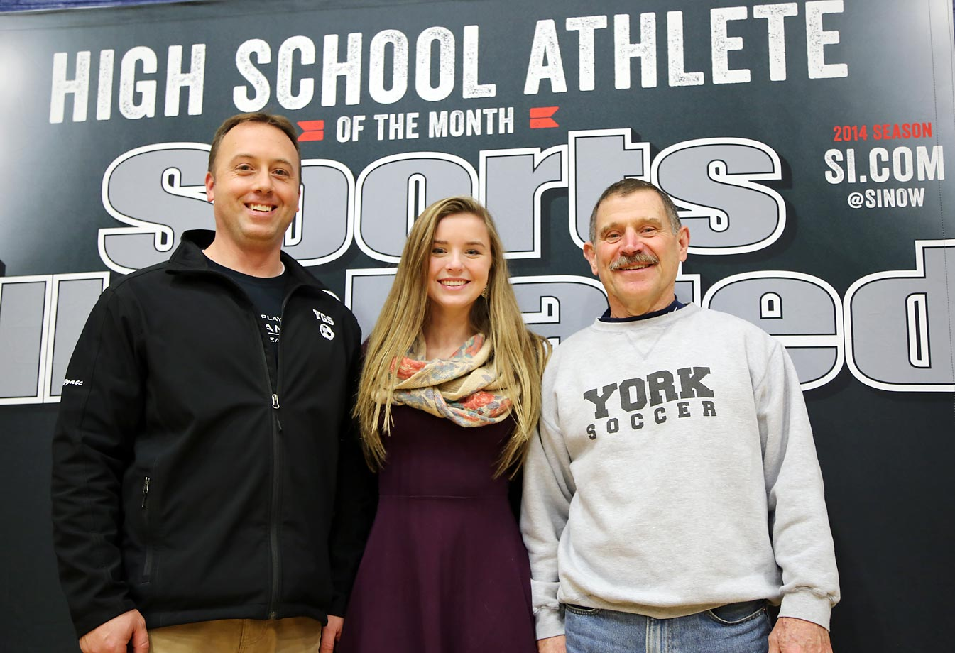 York High girls' soccer jayvee coach Kevin Wyatt (left) and varsity coach Walter Caldwell (right) pose with Kate.