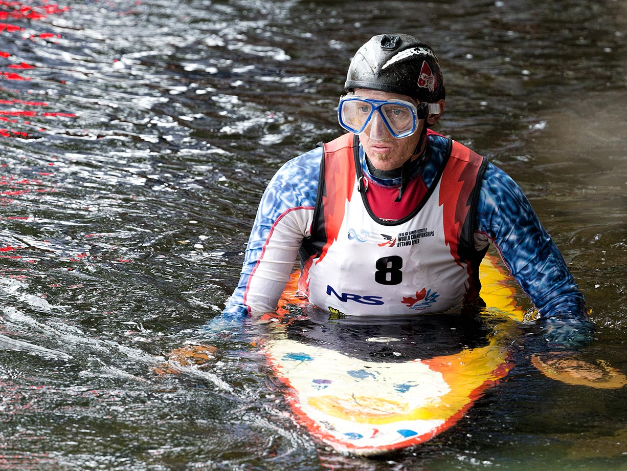 Clay Wright of the U.S. shows how the squirt boat sits below the water, but still holds the kayaker up.