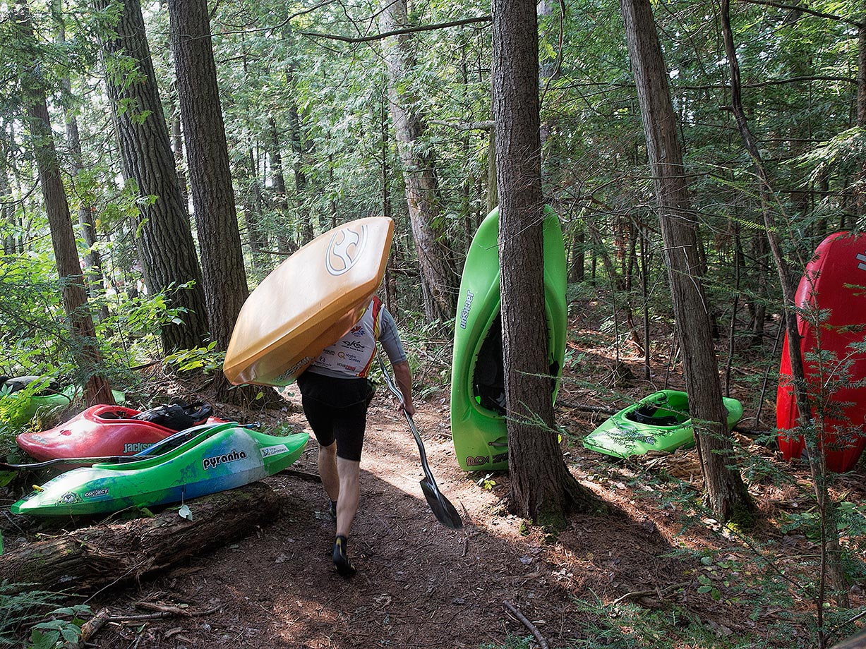 Bryan Kirk of the U.S. and other competitors carry their kayaks.