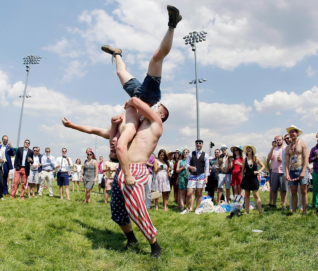 Kentucky Derby fans wrestle in the infield before the 141st running of the Derby.