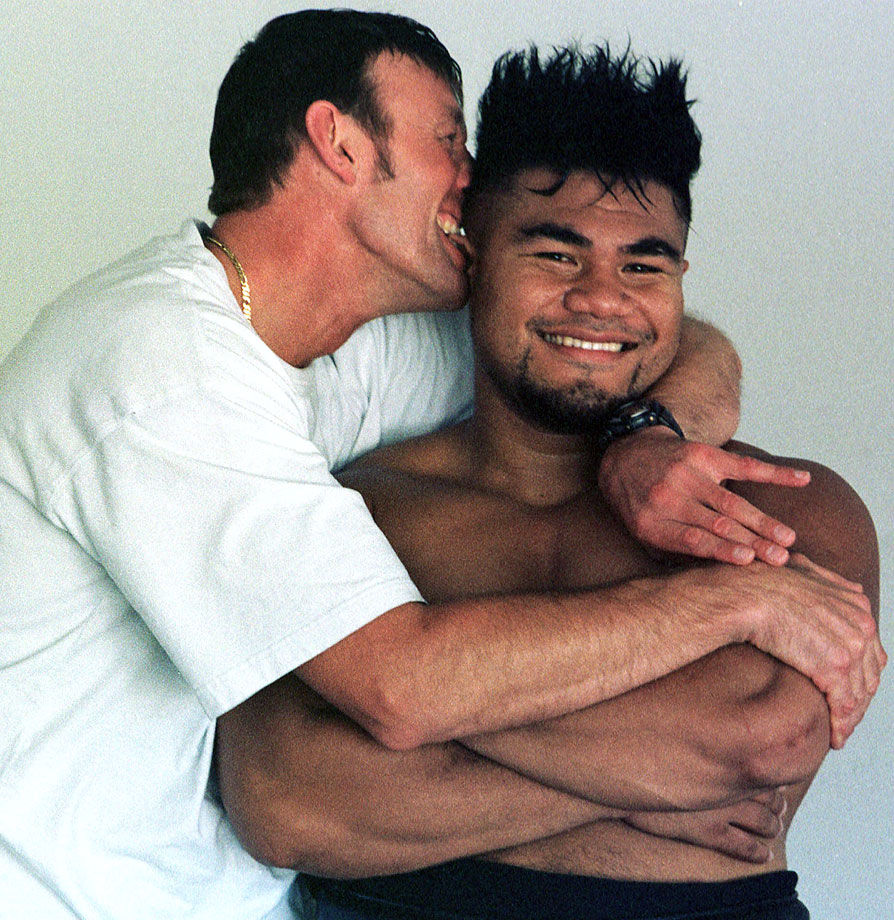 Manager Kevin Barry teases David Tua by nibbling his ear while he posed for photos at a training facility in Las Vegas.